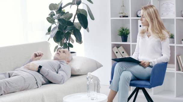 Psychologe schreibt am Cliboard, während reifer Sportler auf Couch liegt