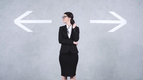 zmatená podnikatelka ukazující gesto pokrčení ramen v blízkosti šipek na šedé