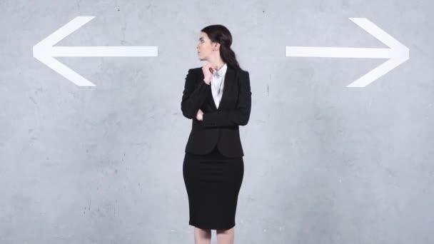 atraktivní podnikatelka výběr mezi šipkami na šedé