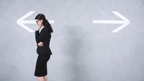 Nachdenkliche Geschäftsfrau geht in die Nähe von Richtungspfeilen