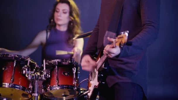 oříznutý pohled rockového kytaristy hrajícího poblíž bubeníka