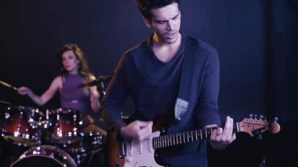 selektivní zaměření kytaristy vystupujícího s bubeníkem