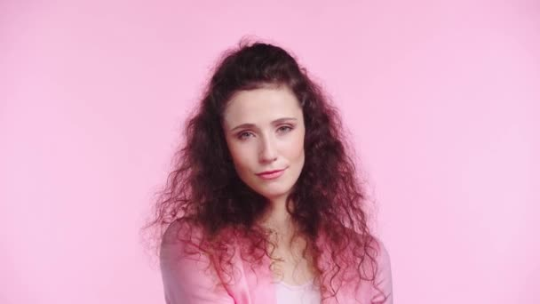serious woman obscuring face with clock isolated on pink