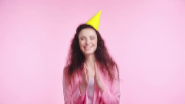 usmívající se žena s party čepice tleskání izolované na růžové