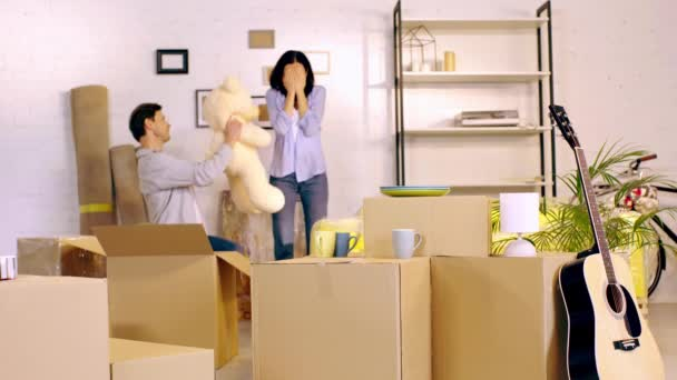 Man giving teddy bear to surprised wife in new home