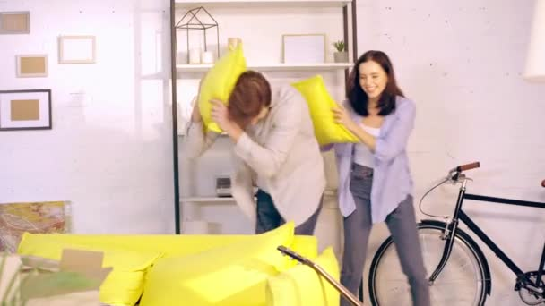 Couple pillow fighting near boxes in new home