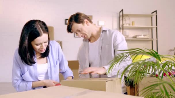 Young couple packing boxes and laughing in living room