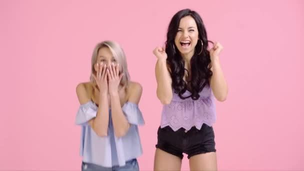 excited girls showing yes gestures and giving high five isolated on pink