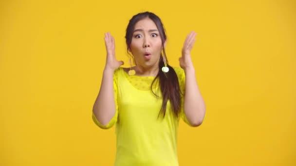schockierte asiatische Mädchen gestikuliert isoliert auf gelb
