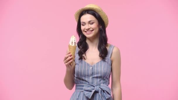 Žena s úsměvem a jíst zmrzlinu izolované na růžové