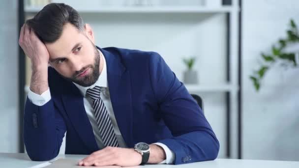 frustrovaný podnikatel v obleku dotýkající se hlavy v kanceláři