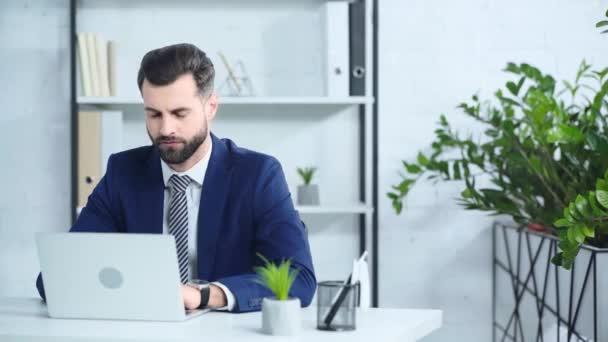 smutný podnikatel v obleku pomocí notebooku v kanceláři