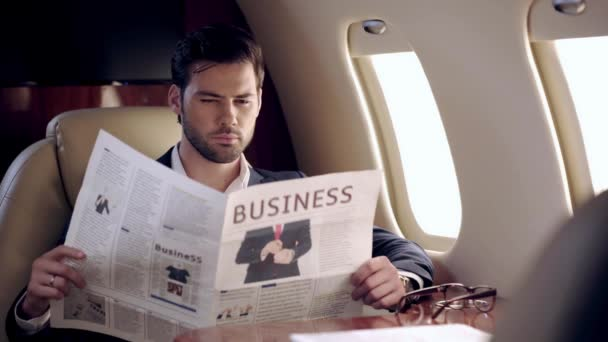 soustředěný podnikatel čtení novin při cestování letadlem