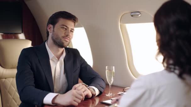Selektiver Fokus von Geschäftsmann und Geschäftsfrau beim Händeschütteln im Flugzeug