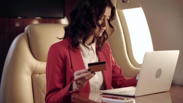 fiatal üzletasszony használja laptop, miközben a kezében hitelkártya a repülőn