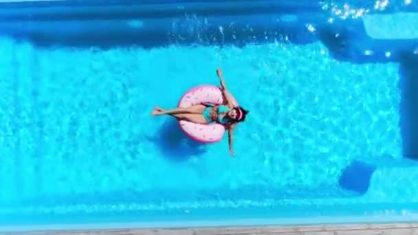 vrchol pohled na šťastnou dívku na koblize plavat kroužek v bazénu v létě
