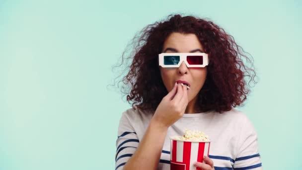 aufmerksames Mädchen in 3D-Brille beim Popcorn essen und Film isoliert auf Türkis ansehen