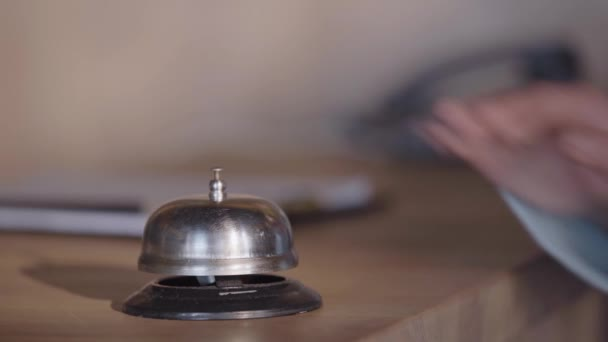 cropped view of woman pressing service bell on hotel reception counter