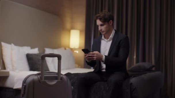 selektivní zaměření mladých podnikatelů chatování na smartphone v blízkosti kufříku