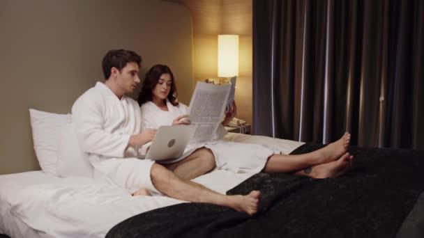 Mann benutzt Laptop und Frau liest Zeitung, während sie sich im Hotelzimmer ausruhen