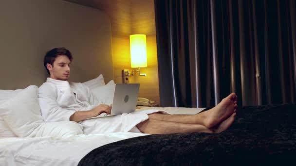 mladý soustředěný muž se usmívá při odpočinku v posteli a psaní na notebooku
