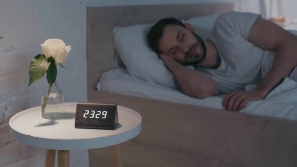 Selective focus of man sleeping on bed at night