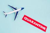 Fotografie Draufsicht auf Spielzeugflugzeug in Papiernähe mit Quarantäne-Schriftzug isoliert auf blau