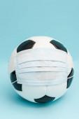 fotbalový míč v lékařské masce na modré