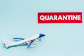 Photo toy plane near paper with quarantine lettering isolated on blue