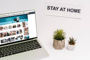 KYIV, UKRAINE - 8 Nisan 2020: bitkilerin ve kağıdın yanında Amazon web sitesi olan dizüstü bilgisayar beyaz harflerle evde kalıyor