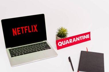 KYIV, UKRAINE - 8 Nisan 2020: Netflix web sitesi ile birlikte yeşil bitki, kalem, defter ve kağıt yakınında beyaz karantina harfleri ile ekranda