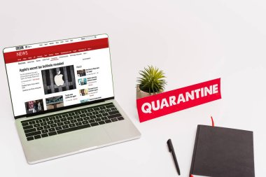KYIV, UKRAINE - APRIL 8, 2020: laptop with bbc news website on screen near green plant, pen, notebook and paper with quarantine lettering on white stock vector