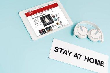 KYIV, UKRAINE - 8 Nisan 2020: kulaklıkların yanında bbc haber uygulamalı dijital tablet ve evde kalıp mavi harflerle yazılmış kağıt