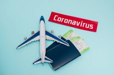 Top view of toy near card with coronavirus lettering and passports with air tickets on blue background stock vector