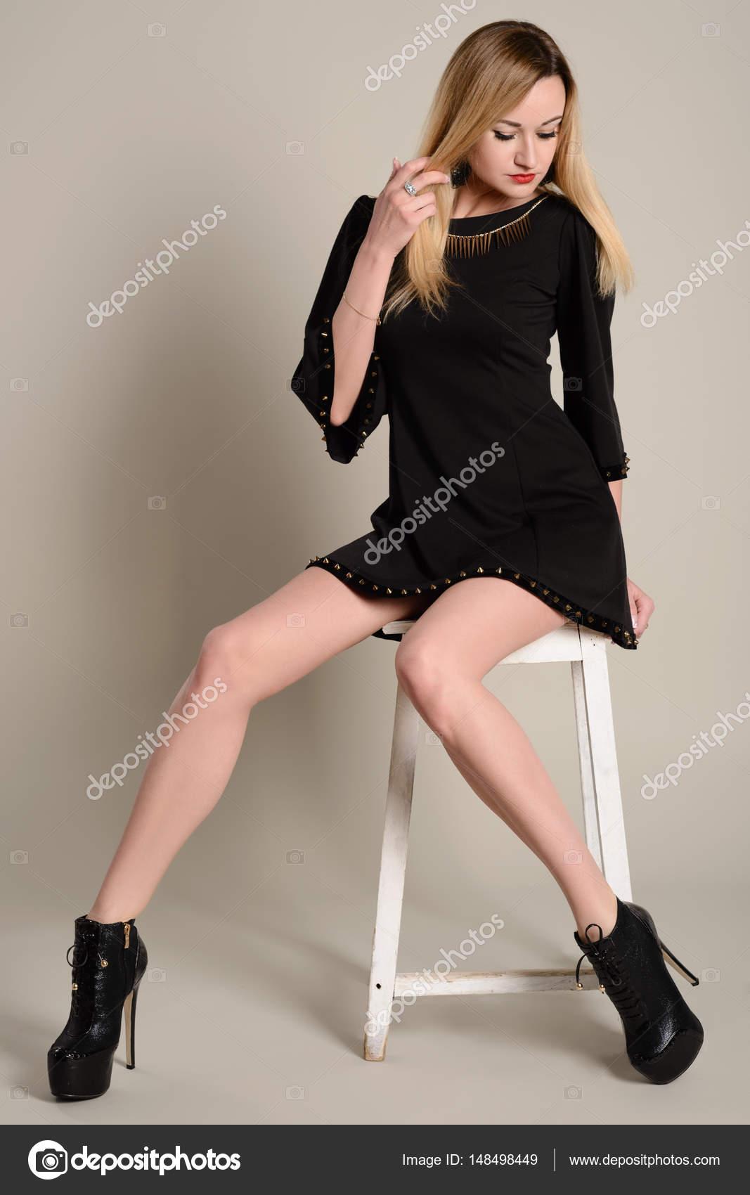 79e31a07bfef Pernas longas Slim menina loira com um vestido preto curto e saltos em um  grampo de cabelo senta-se em um bar stool — Foto de unomay
