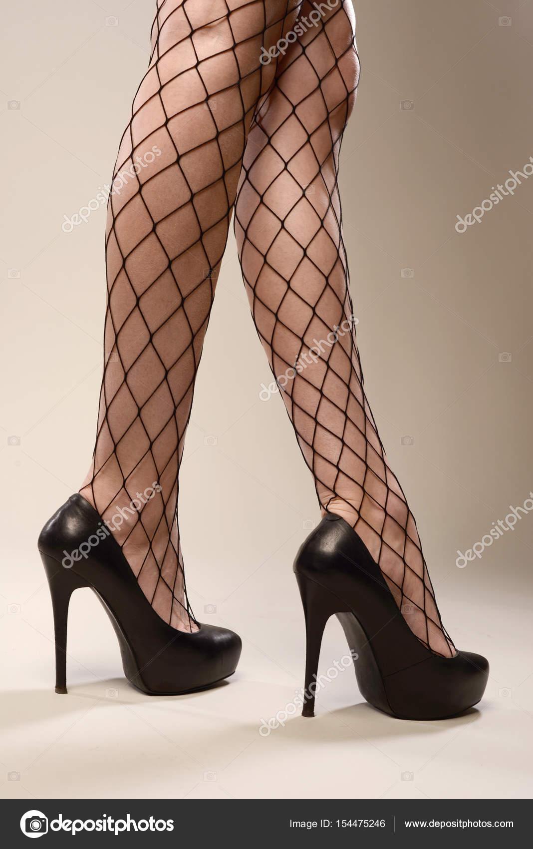 dba0e4605f Piernas hermosas delgadas sexy en medias de red negras y zapatos de tacones  — Foto de