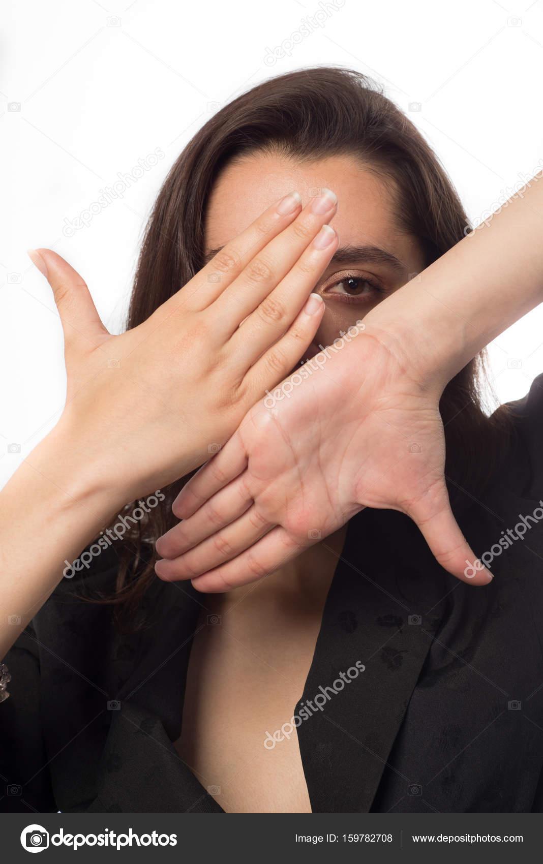 mujer de negocios mirando a través de un marco de mano blanca ...