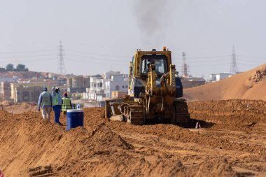 New road construction through the sand excavating and grading the sand preparing for new development in the Middle East
