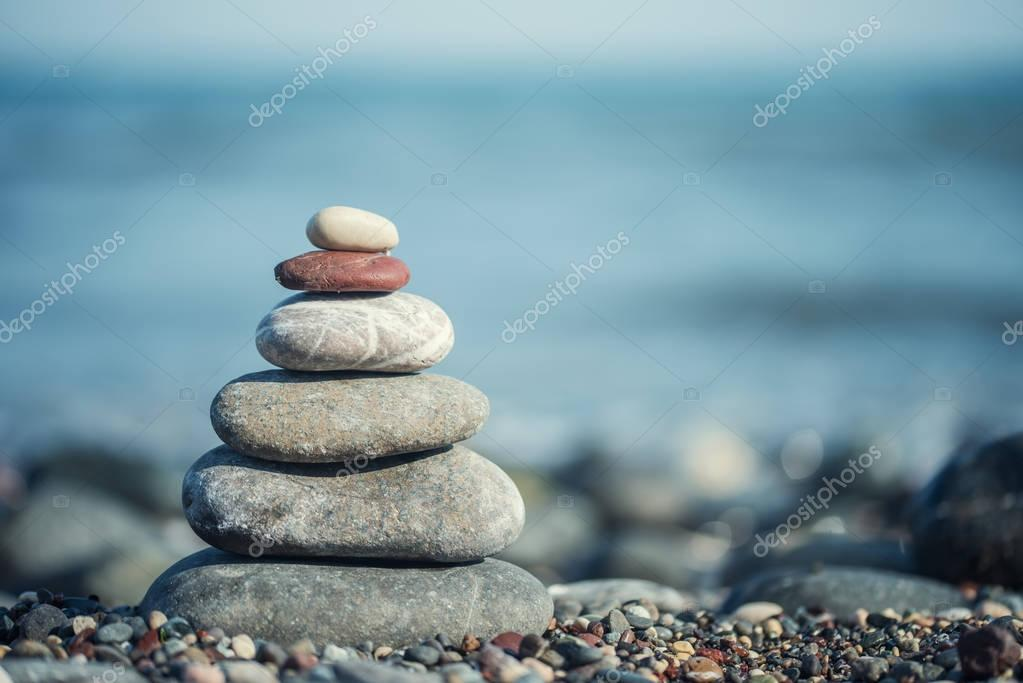 zen-like stones on beach under sun. soft focus