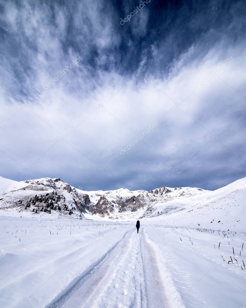 Person walking away down a snowy winter road through country field in a scenic landscape conceptual of the seasons