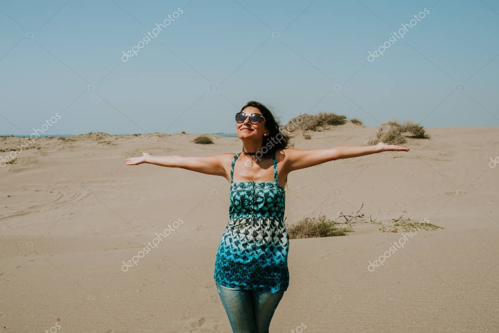 travel, summer holidays, road trip and people concept - happy young woman wearing sunglasses and enjoying sun