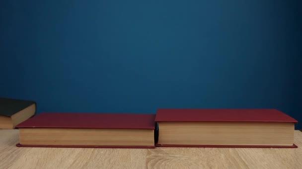 Ruka položí knihy jeden na druhého. Koncept vzdělávání a učení. Koncept knihkupectví
