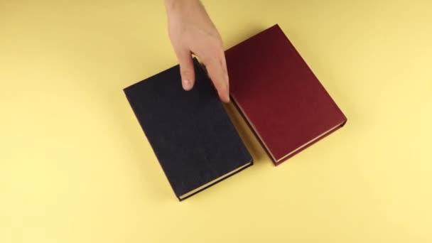 muž ručně umístí knihy ve třech řadách na sebe.