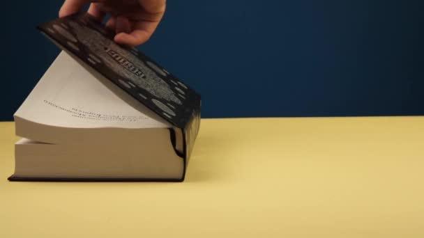 egy férfi kéz nyit egy nagy fekete könyvet, és keresi a megfelelő oldalt. a hit fogalma