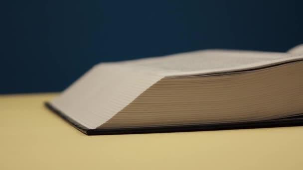 muž otáčí stránky velké černé knihy na modrém pozadí