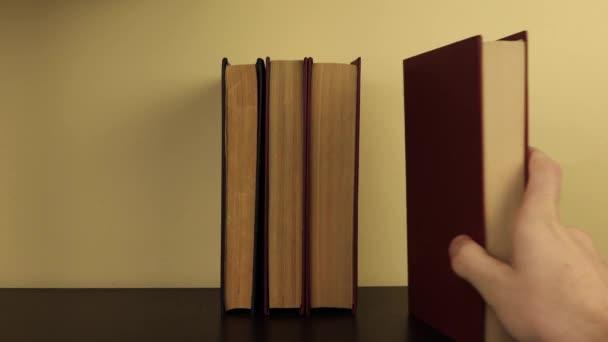 egy férfi kéz felteszi a könyveket a polcra, egyik a másik után, egyenes helyzetben.