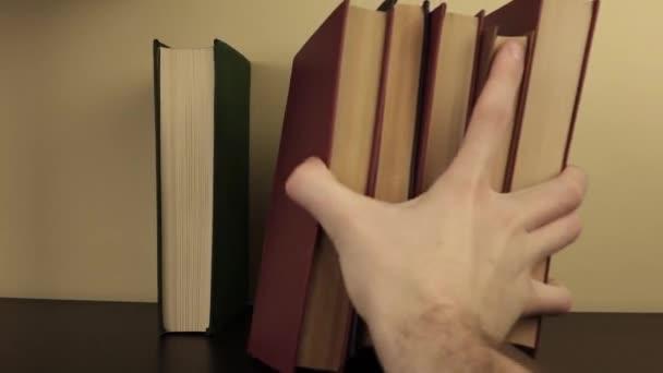 Ein Mann legt einen Stapel Bücher ins Regal