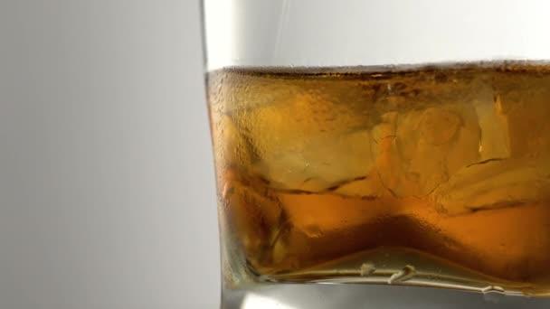 Egy pohár öreg arany whiskey jégkockákkal az asztalon. Borostyán színű alkohol ital kövekkel a bárban