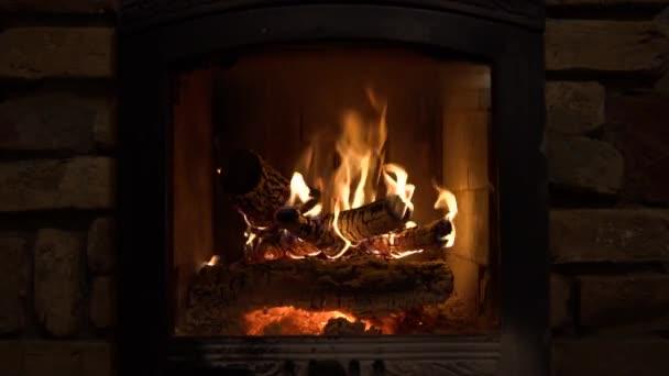 Hořící krb s dřevěnými polena a plameny uvnitř. Teplé světlo, romantická atmosféra uvnitř