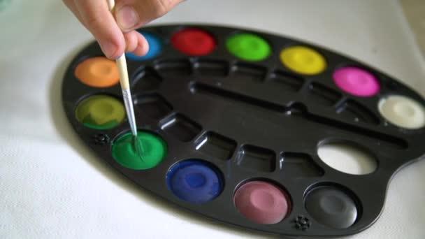 Malý kluk maluje akvarelovou barvou na domácí škole. Detailní záběr ručního namáčení štětcem do barevné barvy. Kreativita a zůstat doma koncept